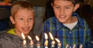 boys lighting menorah