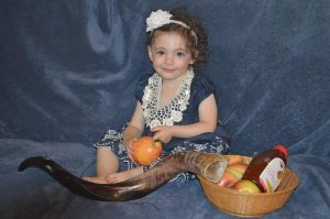 little girl named Kira Berch poses on a blue background wearing a blue dress and holding an apple, next to a basked of apples, a bottle of honey and a shofar